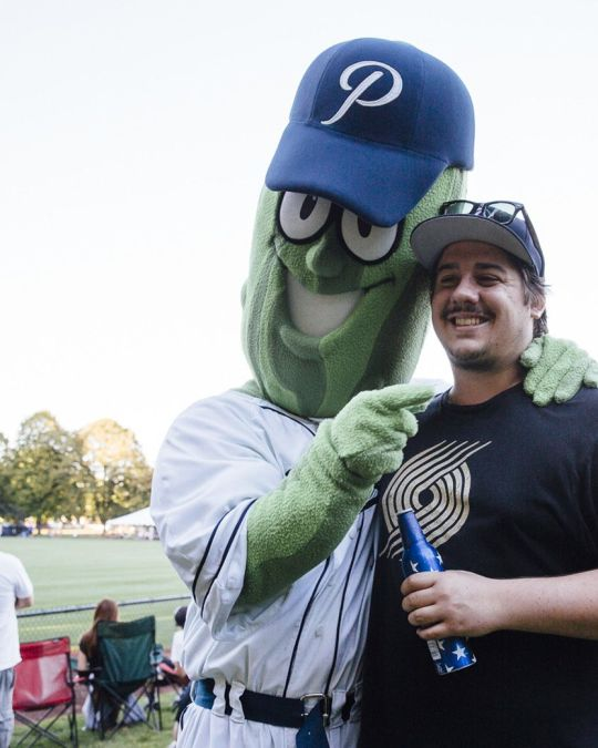 A giant pickle wearing a baseball uniform and hat poses for a photo with a man wearing a Portland Trailblazers shirt