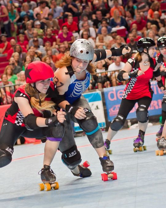 Two opposing roller derby players collide