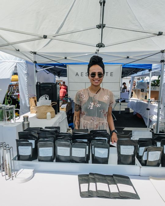 a woman smiles behind a display of beauty products in an outdoor market