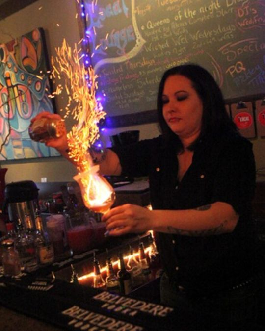 a bartender making a flaming drink behind the bar at Local Lounge