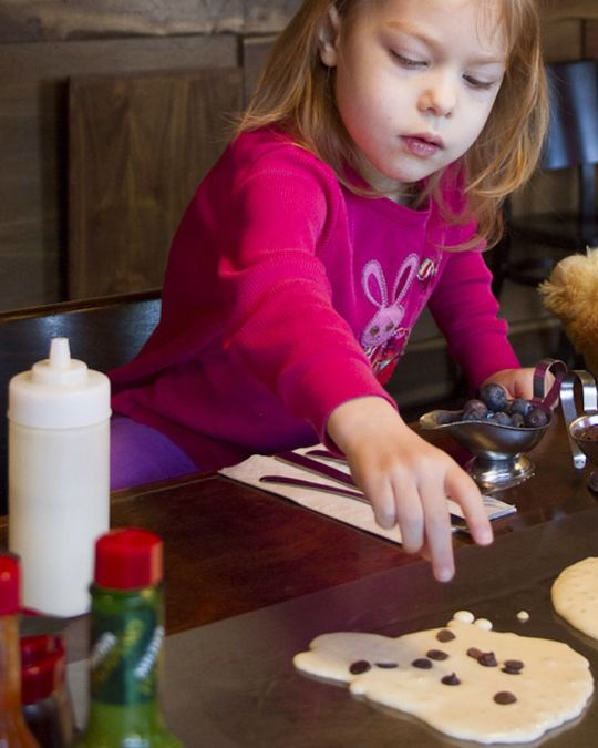 a young girl adds chocolate chips and blueberries to a pancake