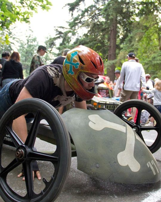 an adult prepares to race a skull and crossbones-styled soapbox