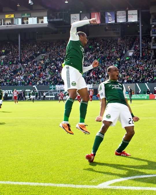 Two Portland Timbers soccer players celebrate on the field after a goal