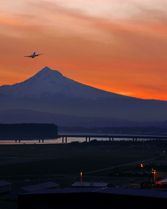the silhouette of a plane against an orange sunset with Mount Hood in the background