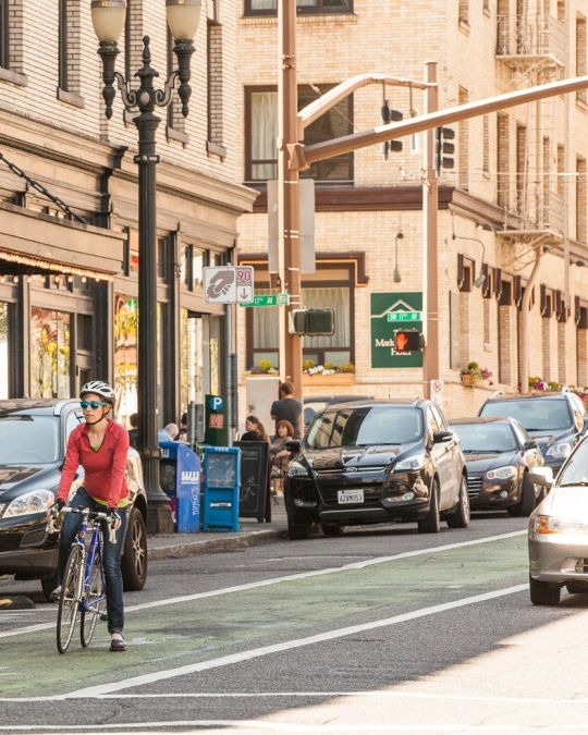 woman riding a bike in a green-painted bike-only lane in downtown