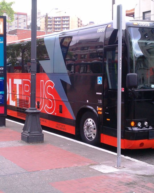 The red and black bolt bus waits curbside for passengers