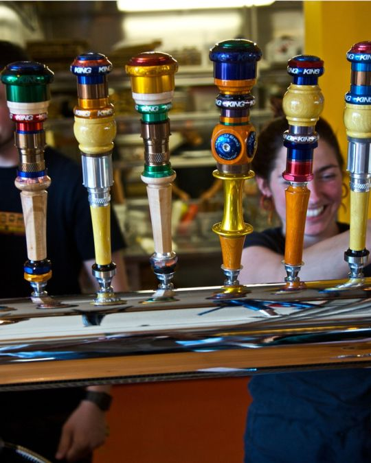 bartenders pouring beer from a line of beer taps at Hopworks Brewery