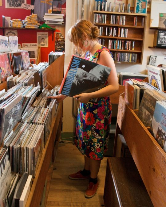 a woman browsing through vinyl albums at Mississippi Records