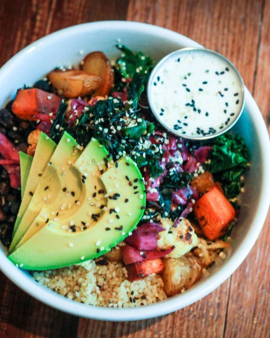 a bowl of brightly colored vegetables with avocado slices on top and a dressing on the side