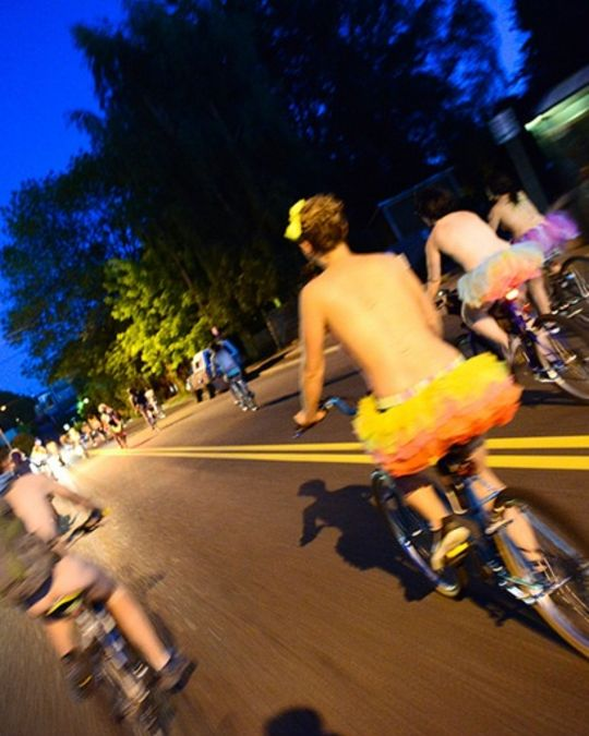people on bikes at night wearing very little clothing
