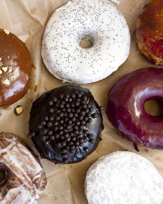 seven gourmet donuts on parchment paper