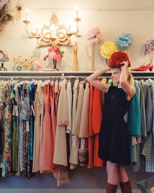 a woman trying on a hat in a clothing store