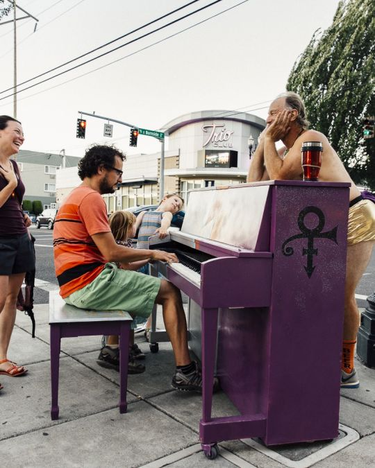 two smiling people gathered around a piano on a street sidewalk, while one person plays the piano