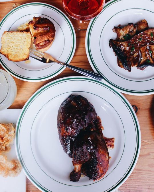 two plates of BBQ and some side dishes
