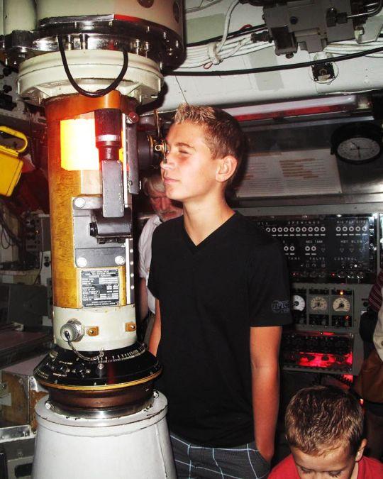 an adolescent boy looking through a submarine scope
