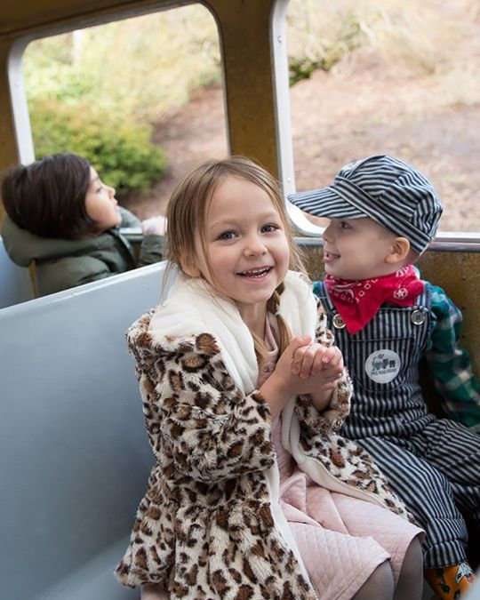 two children sitting on a train, one is dressed like a train conductor
