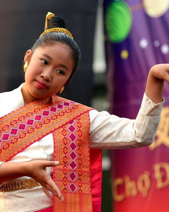 a dancer wearing a colorful sash