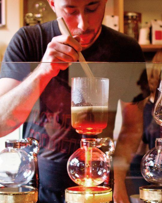 A barista creates a pour-over coffee drink