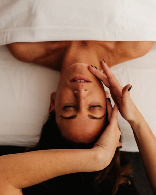 a woman receiving a facial massage at Blooming Moon Spa