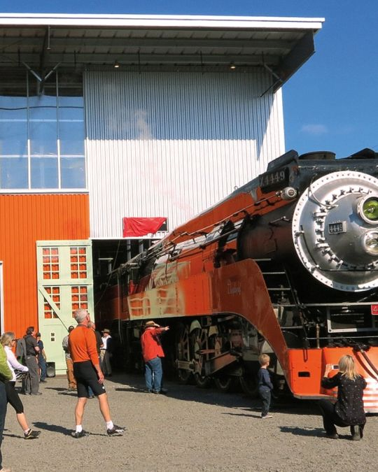 Many people are admiring a bright orange steam engine at the Oregon Rail Heritage Center.