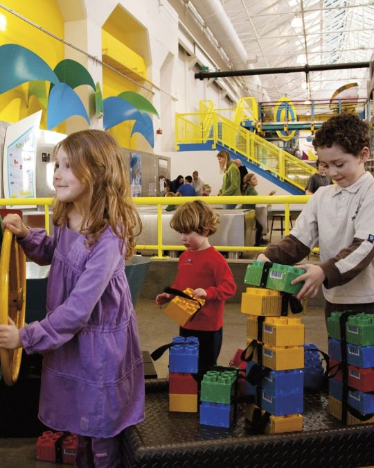 Three kids get hands-on learning with colorful interactive exhibits at OMSI.