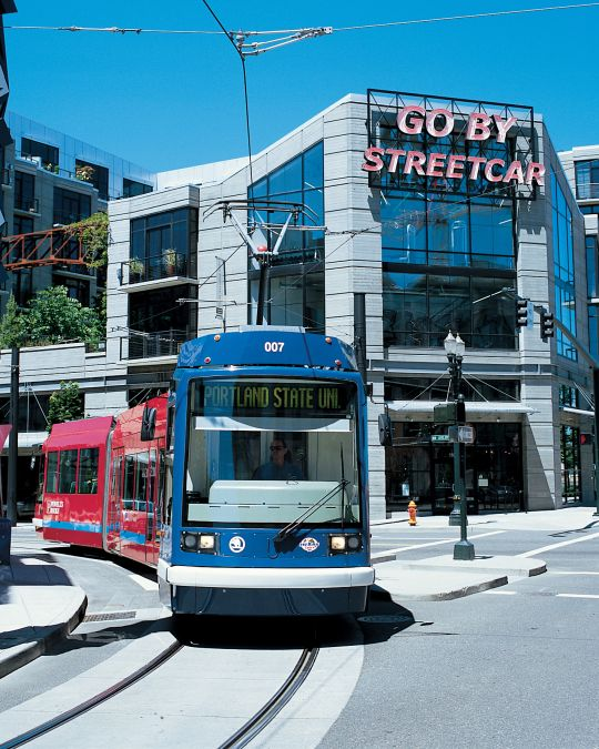 """A streetcar passes by a large, red sculpture in front of a building with a neon sign reading, \""""Go By Streetcar.\"""""""