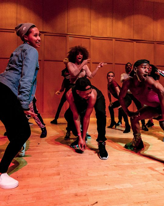 A group of Black people dancing together in a school classroom