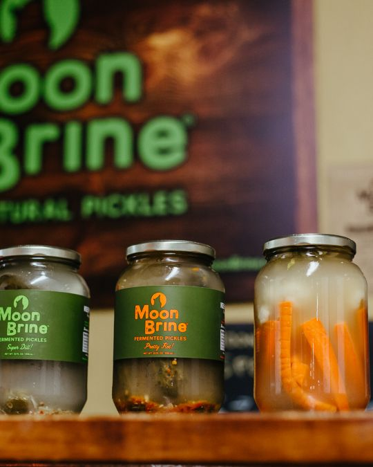 A row of jars of fermented vegetables (including carrots, pickles and beets) from the pickle brand MoonBrine