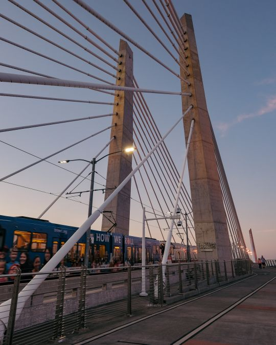 A light rail train crosses a bridge