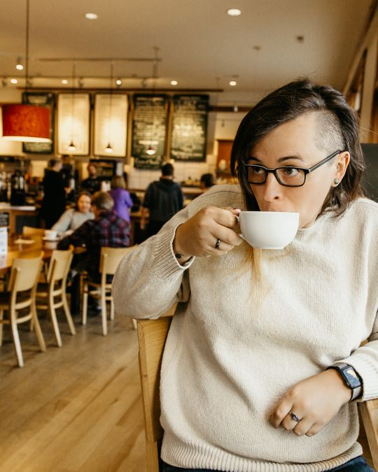 a white person with long hair on one side and a shaved head on the other side, sips from a coffee mug in a warmly lit bakery.