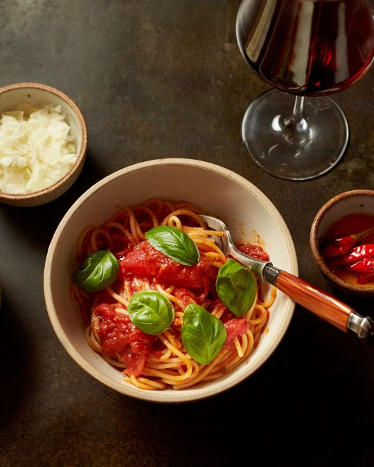 an overhead view of a bowl of pasta, garnishes in ramekins and a glass of wine