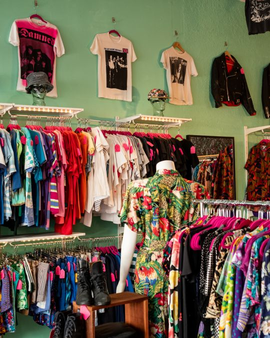 racks of vintage clothing in front of a bright green wall