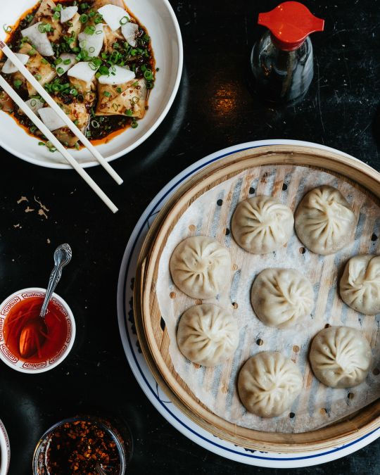 an overhead view of an array of dumplings, tofu and other Chinese dishes on a dark surface