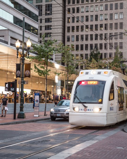 A light rail train passes in front of a modern, glass-encased retail store