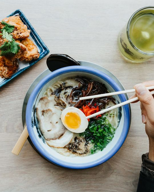 a hand holding chopsticks hovers over a bowl of ramen. a mug of green tea and a plate of fried chicken are next to the ramen bowl on a table.
