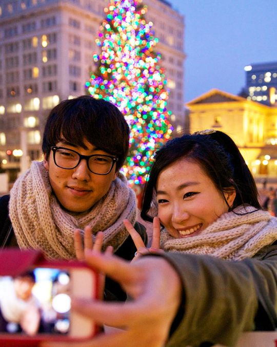 two people taking a selfie in front of portland\'s christmas tree