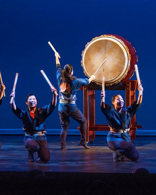 people performing on stage on large traditional japanese drums