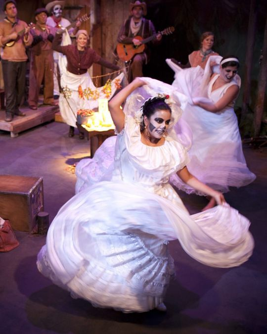 Actors dancing across a stage in long white dresses and skeleton makeup