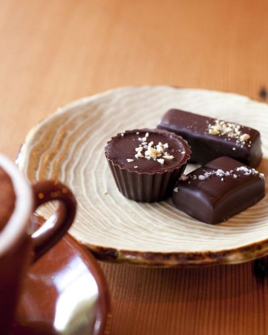 dish of truffle chocolates next to a mug of coffee on a wooden coffee table
