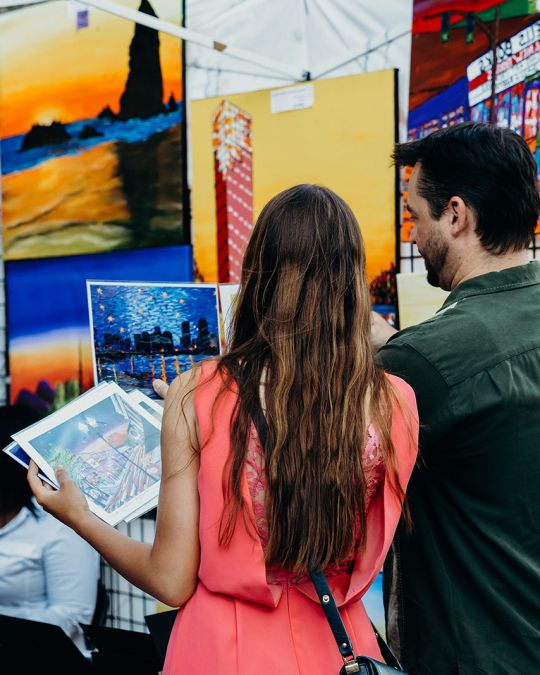 two people look at art on display