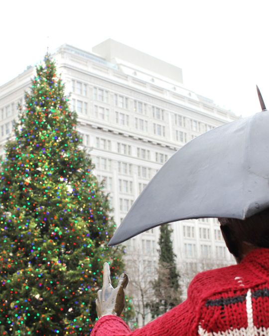 a large tree decorated with lights in front of a statue of a person holding an umbrella