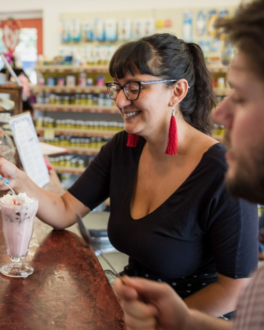 A woman spoons the whipped cream from the top of a milkshake at a pharmacy soda fountain