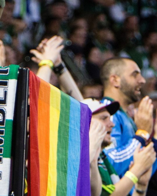 a group of Portland Timbers football fans celebrate at a game