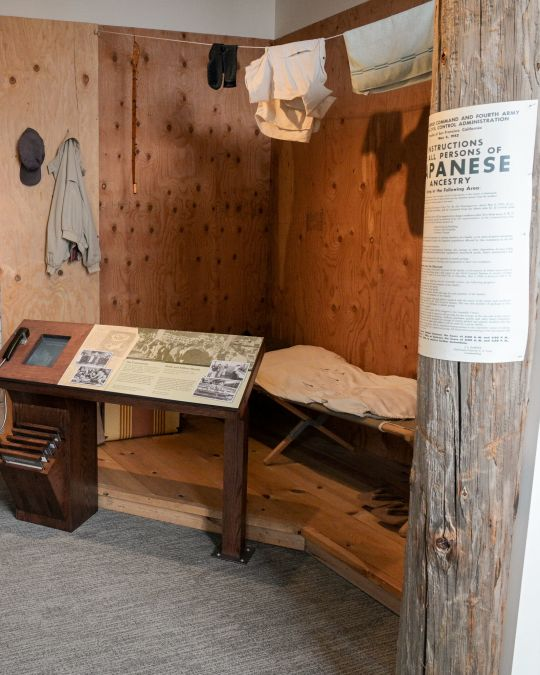 small living space including a cot and hung up laundry with image of a barbed wire fence surrounding, depicting Japanese internment living quarters
