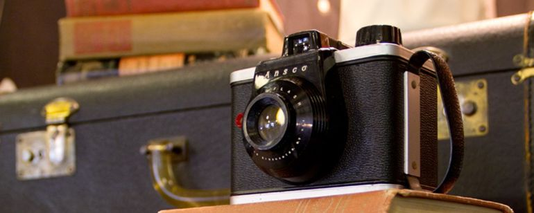 a vintage camera and suitcase displayed along with old hardcover books