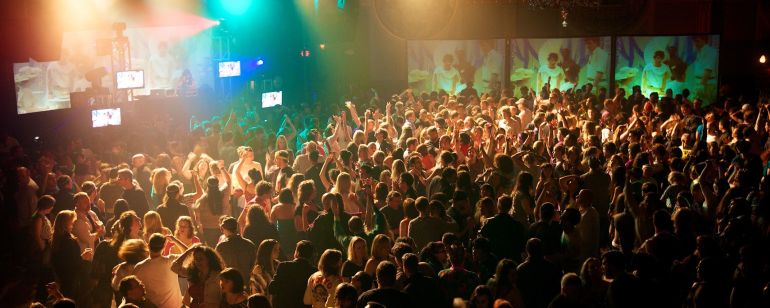 a crowd of people dancing in a night club