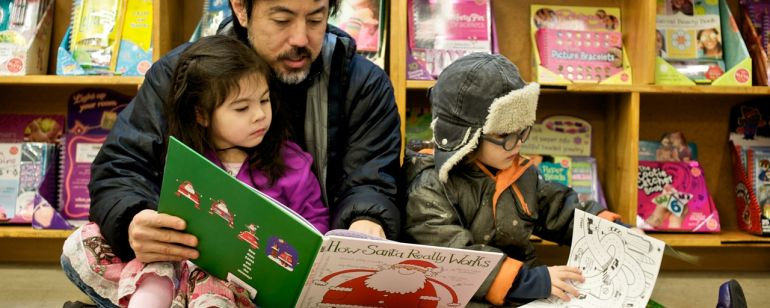 A family sitting on the floor reading children's books at Powell's City of Books.