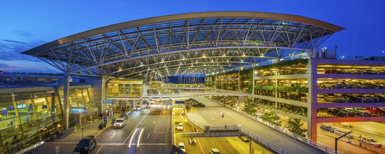 metal and glass canopy over Portland Airport entrances lit up at night