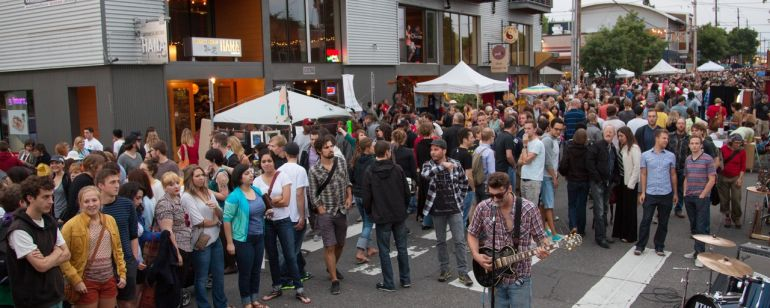 crowd gathered around a street musician as he performs at Last Thursday art walk