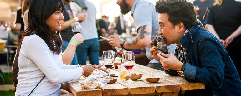 two people eating food and drinking wine at a picnic table
